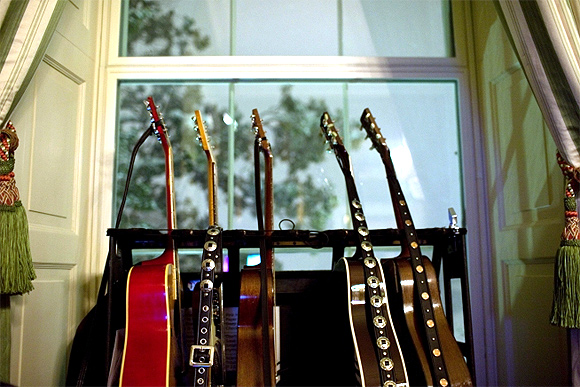 Guitars rest in a rack in front of a window in the Green Room of the White House