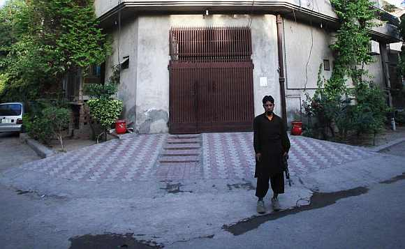 A private security guard stands outside the residence of Saeed