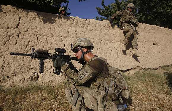 US army soldiers from Charlie company 4th platoon,1st brigade 3-21 infantry, jump over a wall during a patrol in the village of Chariagen in the Panjwai district of Kandahar provin