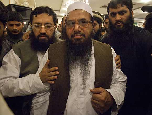 Hafiz Saeed, the head of Jamaat-ud-Dawa and founder of Lashkar-e-Tayyiba, is surrounded by his supporters as he leaves after a news conference in Rawalpindi near Islamabad