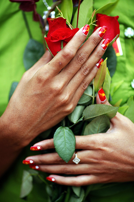 A supporter with nails painted in the NLD's colours holds flowers for Aung San Suu Kyi.
