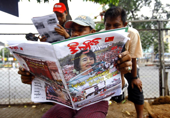 People on a walkway in Yangon read a newspaper announcing Suu Kyi's victory