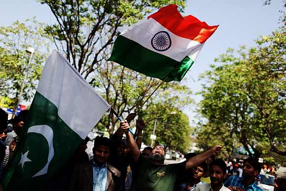 Indian and Pakistan fans wave their flags during a cricket match in Mohali
