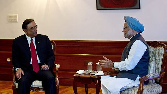 Prime Minister Manmohan Singh gestures while speaking with Pakistan President Asif Ali Zardari during a meeting in New Delhi