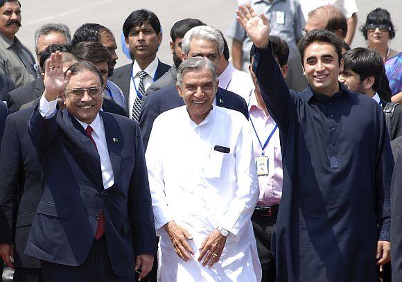 Pakistan's President Asif Ali Zardari gestures as his son Bilawal Bhutto Zardari waves upon their arrival at the airport in New Delhi