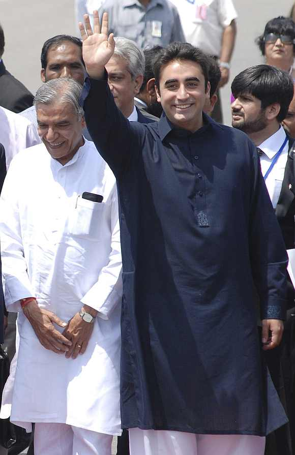 Bilawal Bhutto Zardari waves upon their arrival while Parliamentary Affairs Minister Pawan Kumar Bansal looks on at the airport in New Delhi