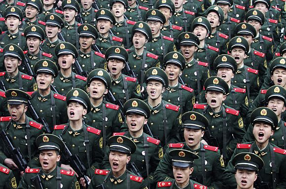 Recruits of the Chinese Army shout slogans during a handover ceremony on a rainy day at a military base in Hangzhou