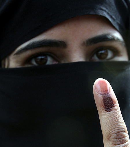 A voter displays her finger after casting her ballot in Kashmir.