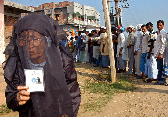 A Muslim woman holds up her voter's identity card in Patna