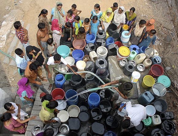 Residents fill their containers with drinking water from a water tanker provided by the Rajasthan government in Jaipur