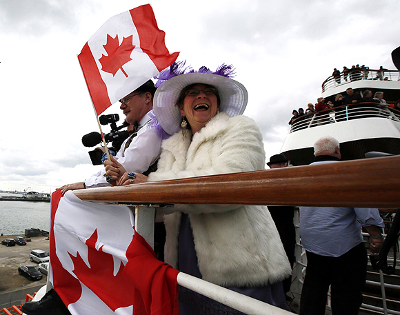 Bernadette and Brice Christie of Grande Prairie, Alberta stand with Canadian flags as the Titanic Memorial Cruise leaves port in Southampton