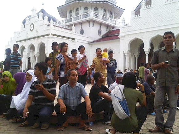 People gather outside the Baiturrahman mosque after the quake