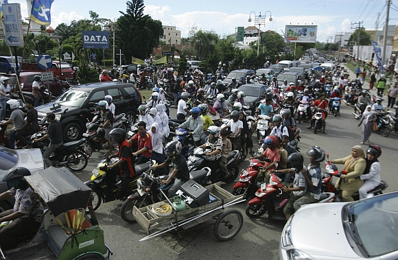 People riding motorbikes and cars packed the street in Banda Aceh  after the quake