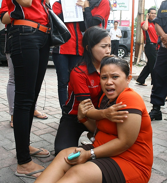 Office workers panic as they evacuate and gather in front an office building in Medan after the quake