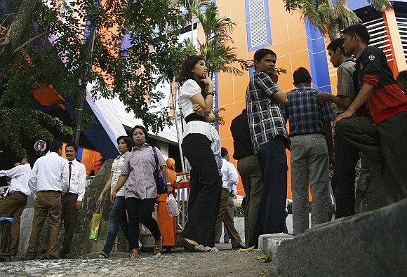 Office workers evacuate and gather in front an office building in Medan after the quake