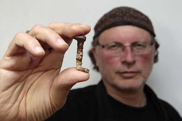 Veteran investigator Simcha Jacobovici holds one of the two nails presented in his new documentary film as having a connection to Jesus at Tel Aviv University on April 6. The film