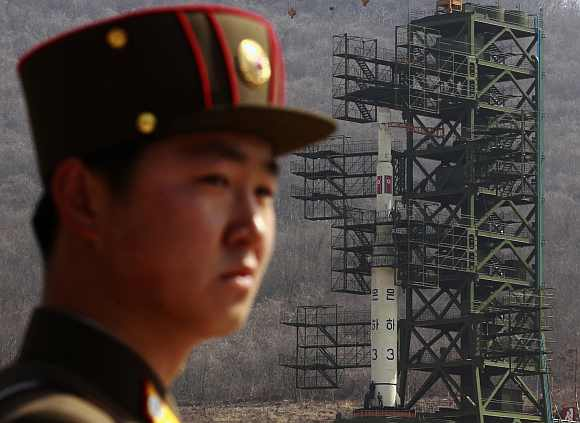 A soldier stands guard in front of the rocket sitting on a launch pad at the West Sea Satellite Launch Site, during a guided media tour by North Korean authorities in the northwest of Pyongyang
