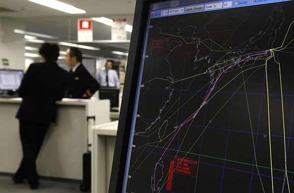 Japan Airlines pilots look at a monitor next to a computer screen showing no-fly zones in red, as well as a new route that would avoid an accident with North Korea's planned long-range rocket launch in a Japan Airlines' pilot ready room at Haneda airport in Tokyo