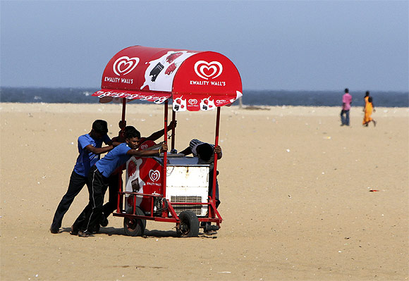 People move an ice-cream cart from the Marina beach after a tsunami alert was issued in Chennai