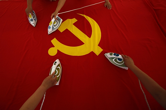 Workers use electric irons to smooth out a Communist Party of China flag on a table at the Beijing Jingong Red Flag factory, located on the outskirts of Beijing