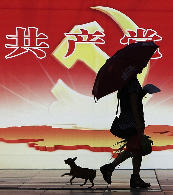 A woman and a pet dog walk past a poster depicting the logo of the Communist Party of China in Chongqing municipality