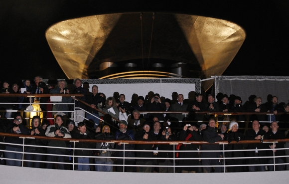 Passengers stand on upper decks and view a service of remembrance aboard the Titanic Memorial Cruise