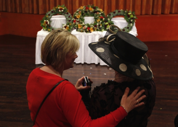 Helena Beaumont-Jones of Airlie Beach, Australia is embraced by Titanic Memorial Cruise general manager Tara Plumley while viewing three wreaths before a memorial service on board
