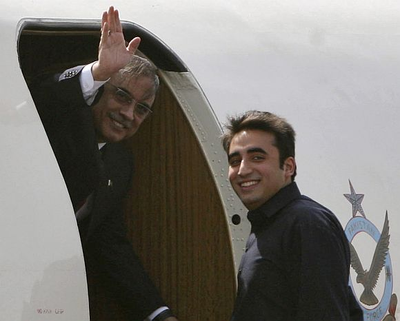 Pakistan's President Zardari waves as his son Bilawal looks on before they depart for Jaipur at the airport in New Delhi on April 8