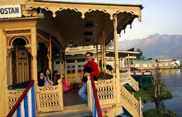 Tourists rest on the deck of a houseboat on the waters of Dal Lake in Srinagar