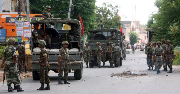 Army soldiers stand guard during a protest in Jammu
