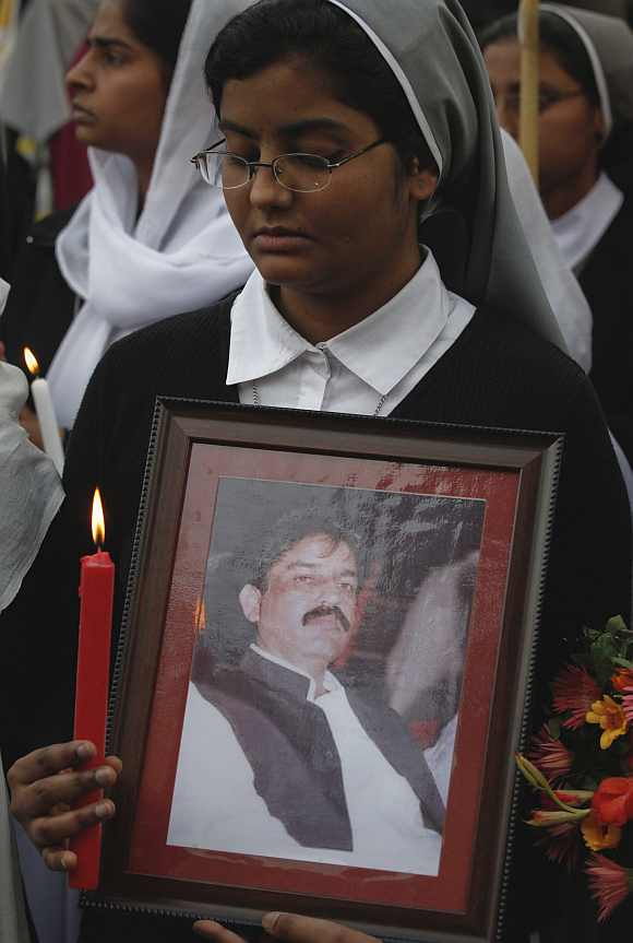 A Christian holds a picture of slain Minister for Minorities Shahbaz Bhatti during a candlelight vigil in Lahore March 12, 2011. Bhatti, the country's only Christian government minister, was killed on March 2 for challenging a law that stipulates death for insulting Islam