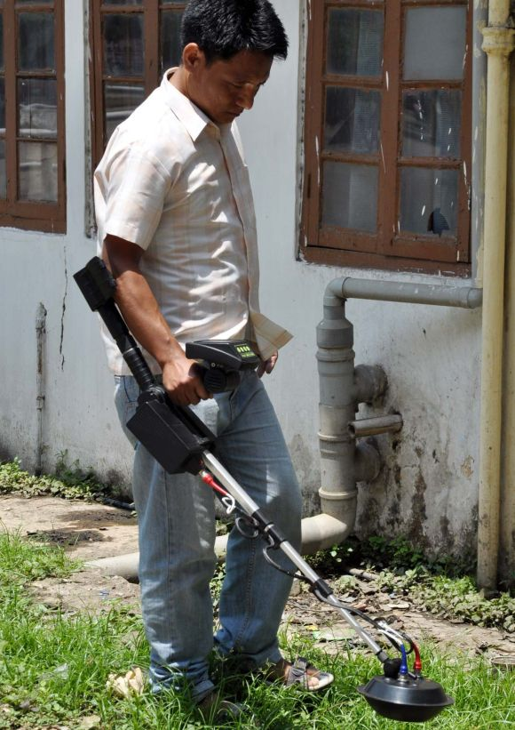 A police official uses anti-landmine device to survey ahead of PM's visit in Guwahati