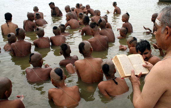 Brahmins perform prayers in the waters of the Sangam