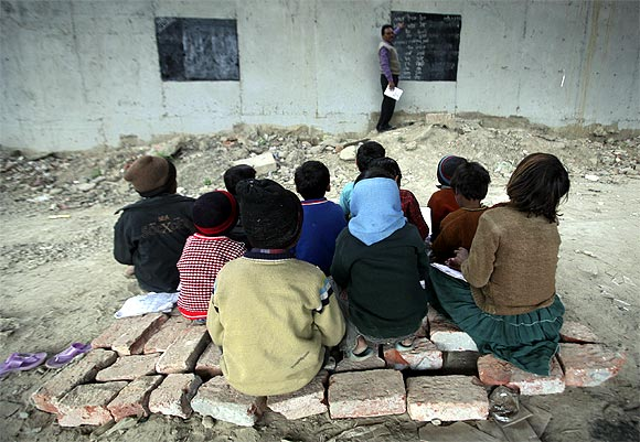 Children sit on bricks as they attend their class in an open charitable school
