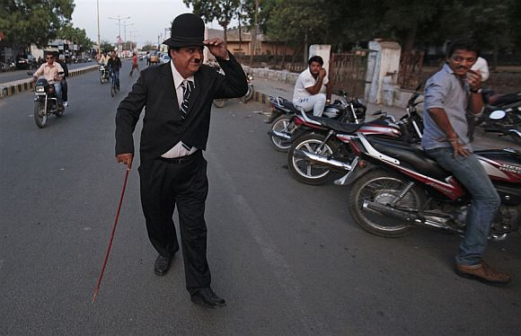 Ashok Aswani, in costume as Charlie Chaplin walks on a road in Adipur