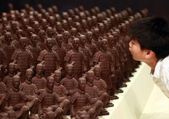 A boy looks at chocolate Terracotta Warriors displayed at the World Chocolate Wonderland in Taipei