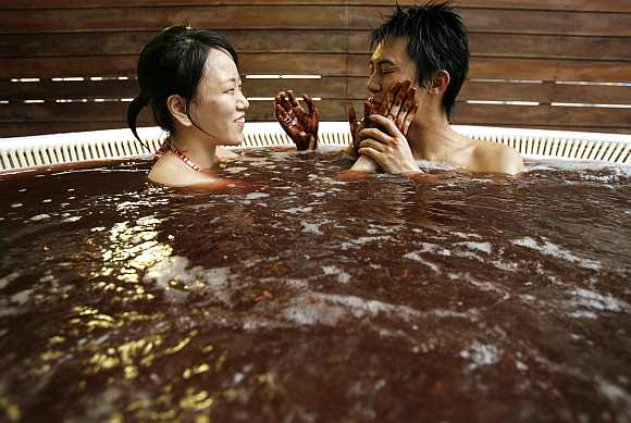A woman spreads chocolate on her boyfriend's face in a bath incorporating chocolate at a hot springs spa resort in Hakone, west of Tokyo