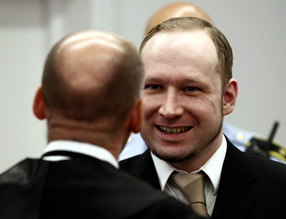 Defendant Anders Behring Breivik discusses with his defence lawyer Geir Lippestad in the courthouse in Oslo