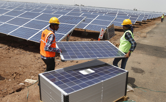 Workers carry photovoltaic solar panels for installation at the Gujarat solar park