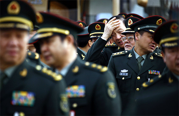 Members of the People's Liberation Army stand together as they arrive at the Great Hall of the People for a session of the National People's Congress, China's annual parliament, in Beijing
