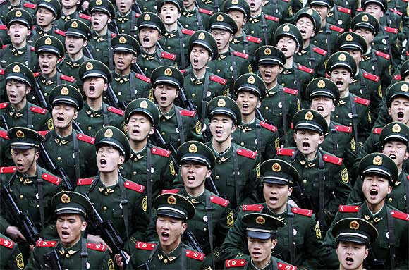 Recruits of the People's Liberation Army shout slogans during a handover ceremony on a rainy day at a military base in Hangzhou, Zhejiang province