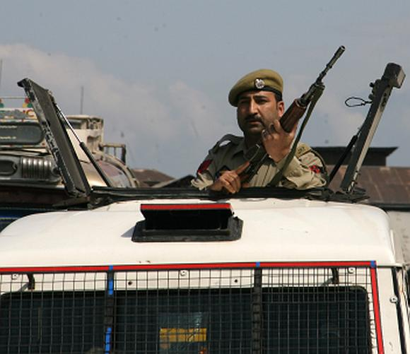 A policeman keeps a close watch at the site where an ASI was shot by militants