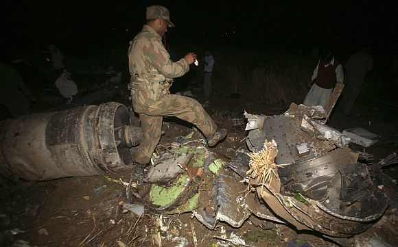 An army soldier walks through the wreckage of the Boeing 737 airliner which crashed in Islamabad