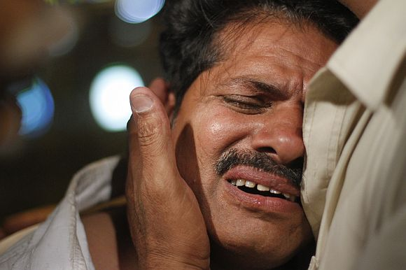 A relative of a victim of the Bhoja Air airliner crash mourns at the Jinnah International Airport in Karachi