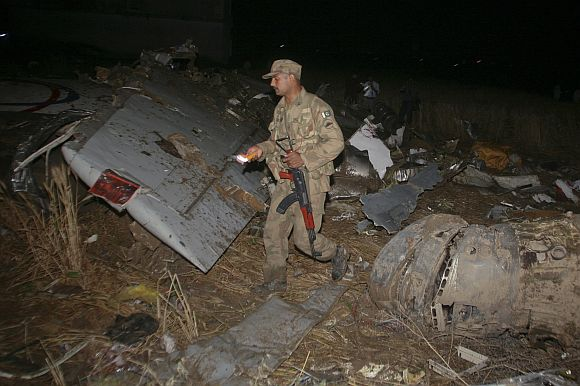 An army soldier walks through the wreckage of the Boeing 737 airliner