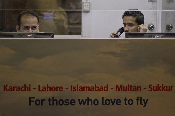 Bhoja Air employees sit behind computers in a ticket booth at the Jinnah International Airport in Karachi