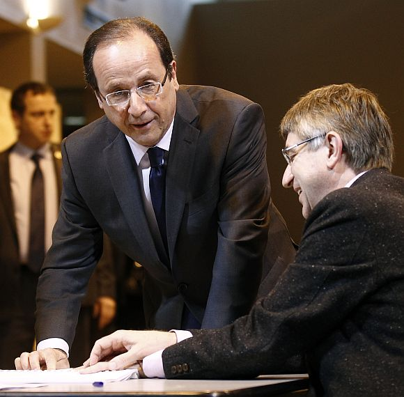 Francois Hollande signs the electoral register after casting his ballot in the first round of 2012 French presidential election at a polling station in Tulle
