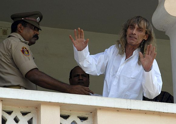Freed Italian tour guide Paolo Bosusco, who was taken hostage by Maoist rebels, waves from a balcony of a guest house in Bhubaneswar