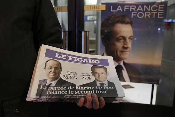A newspaper hawker displays an early edition of Le Figaro outside the Mutualite meeting hall in Paris after the first round of the 2012 French presidential election