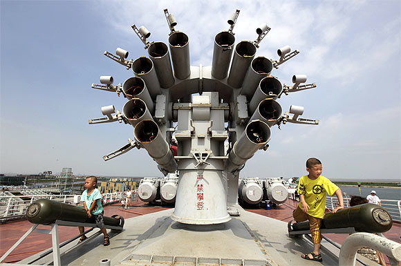 Children play next to a rocket launcher on the decommissioned former Soviet aircraft carrier Kiev at Bagua beach, on the outskirts of northern China's Tianjin